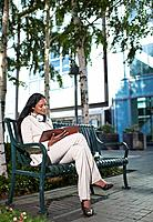 Businesswoman Looking at Notebook on Bench