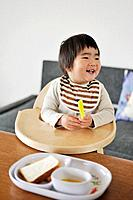 Baby boy sitting in high chair, smiling