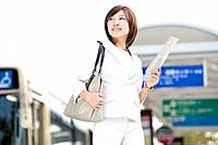 Businesswoman holding newspaper at bus stop