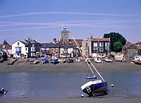 River Colne estuary. Town. Mud flats. Boats/ yachts beached. Quayside pub/ shop/ houses.