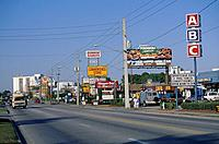Downtown. International Drive. Roadside signs. Red/ yellow. Advertising restaurants/ stores. Cars.