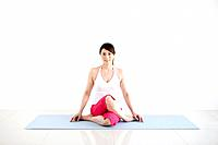 Mature Woman Sitting Cross_legged on Exercise Mat