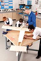 Teacher and students working on large wooden model airplane in woodworking class