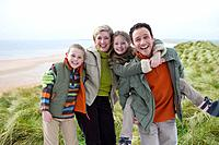 Portrait of smiling family in warm clothing on beach
