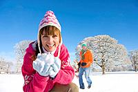 Portrait of smiling woman holding snowball in field with man and sled in background