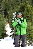 Portrait of smiling man with ski poles in snowy woods