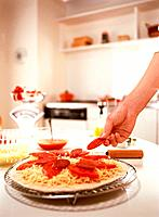 Woman preparing tomato and pepperoni pizza