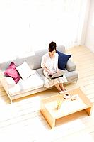 Woman using laptop on sofa in living room
