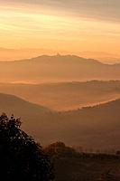 Sunrise over Tiber valley with orange and golden sky in the early morning mist of winter, with tree outline in foreground, and hilltop town of Todi in...