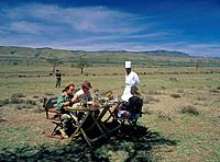 Bush breakfast on the plain. Table and chairs. People. Champagne. Chef in white. Armed guard.