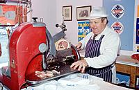 Traditional butcher´s shop. Butcher in striped apron and hat slicing meat with machine.