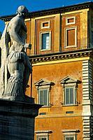 Statue of Marcus Aurelius in the Campidaglio courtyard. Orange/ brown building behind.