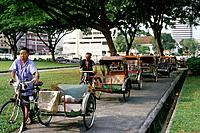 A line of rickshaw/ trishaw drivers with their bicycles,queueing for customers on the Padang outside the Cricket club. Public transport in the city ce...