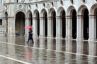 Colonnade of inside courtyard of Doges Palace and person walking in rain with red umbrella