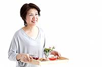 Mature woman carrying a tray of food and tea