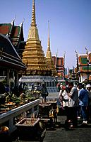 Grand Palace temple complex. People worshipping at shrine. Offerings/ incense.