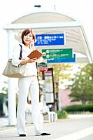 Businesswoman holding personal organizer at bus stop