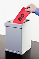 A man putting a ballot with the word NO written on it into a ballot box, close_up hands