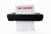 A document with TOP SECRET on it being shredded in a paper shredder