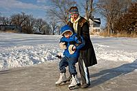 A young girl helps her brother ice skate on a farm near Dunbar, NE.