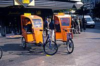 Two tricycle velo taxis. Bright orange cabs for passengers.