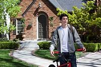 Boy standing still holding bike outside his house