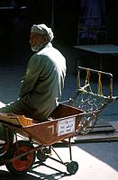 Market. Man,licenced market porter seated on trolley.