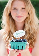 Young woman holding carton with organic blueberries