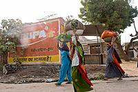 Indian women carry loads of vegetables on their heads.