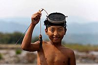 A little boy uses a basic mask to catch fish in the river