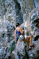 Krabi Laem Phra Nang. Woman in climbing harness on cliff face.