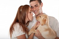 Young couple with labrador retriever puppy
