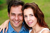 Young couple smiling looking at camera.