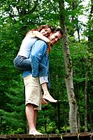 Young couple playing piggyback.
