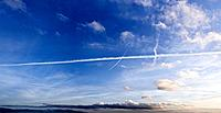 A panoramic blue atmospheric sky with a few gentle clouds and a distinct vapor trail across the center of the image