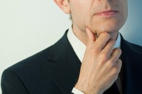 Thoughtful man, hand on chin. Close view