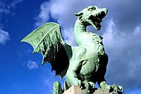 Dragon bridge. Statue of dragon in bronze. Wings outstretched. Symbol of strength. Green metal. Oxidized.