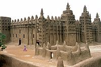 City built of mud. Mosque. Rounded wall shapes. Iron spikes on walls. Man in pink robe walking in courtyard.