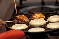 Aebleskiver Danish meaning apple slices singular: Aebleskive are traditional Danish pancakes in a distinctive shape of a sphere.