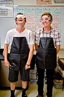 Two happy high school chemistry students in San Clemente, CA, are equipped for a laboratory experiment wearing safety goggles and rubber aprons  Note ...