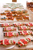 Decorated Christmas cookies on a table, in shapes of Santa Claus, angels, and trees