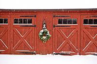 Holiday wreath hanging on red wooden barn. Snow falling and accumulating on wreath, barn, and ground.