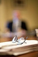 Folded eyeglasses on papers on conference table at business meeting. Blurry shape of person in background.