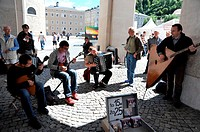 Group of young people playing balalaika and accordion and man selling CD albums in the Domplatz Square's colonnades, Salzburg, Austria