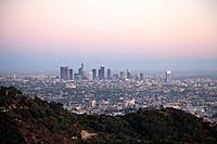 Landscape view of skyscrapers of downtown LA with hills of Griffith Park in foreground as seen at sunset
