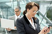 Mature businesswoman texting on cell phone, businessman with laptop in background