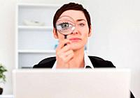 Office worker looking through a magnifying glass in her office