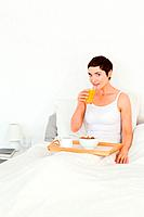 Portrait of a woman drinking juice for breakfast in her bedroom