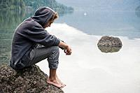 a young man sits on a rock in cameron lake, british columbia canada