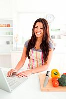 Charming woman relaxing with her laptop while standing in the kitchen